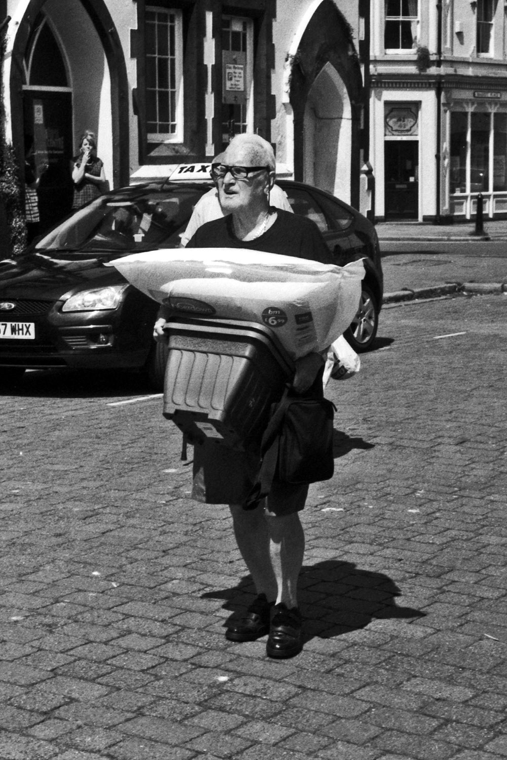 old man in shorts carries packages whitehaven street photography uk photographer kevin shelley prints for sale leica m2 jupiter 8 50 f2