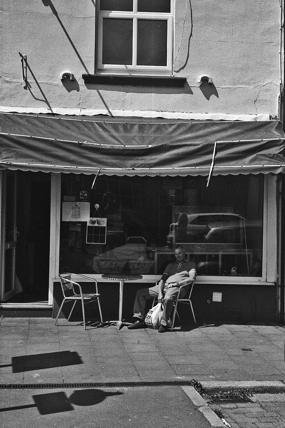 man sat outside cafe whitehaven street photography uk photographer kevin shelley prints for sale leica m2 jupiter 8 50 f2
