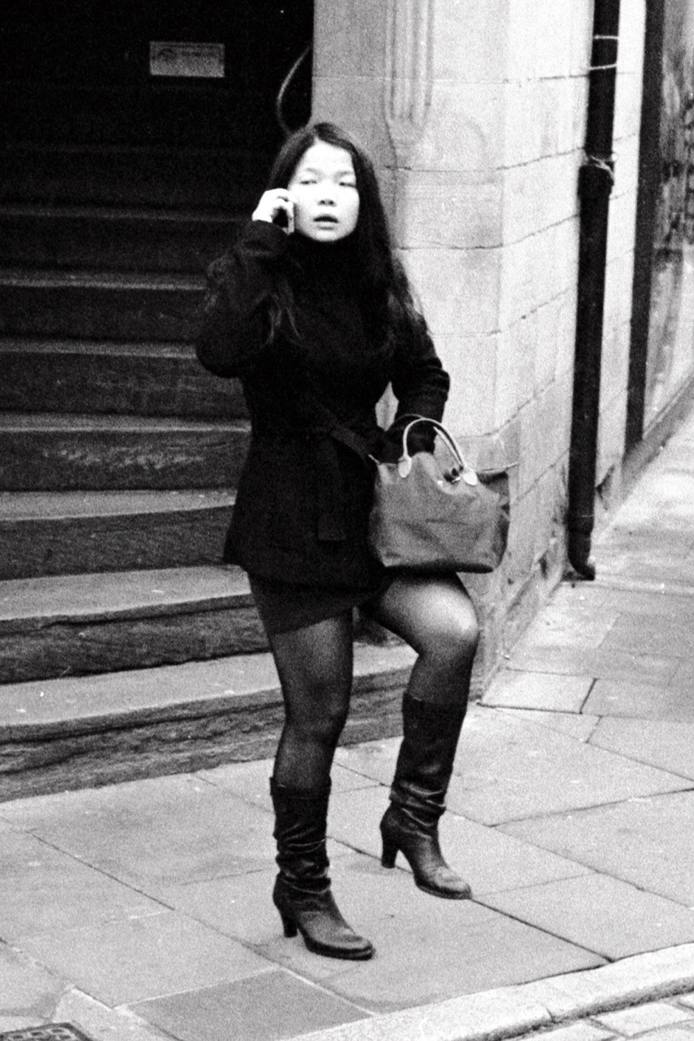 asian lady talks on phone rummages in handbag and stands on one leg chester street photography uk photographer kevin shelley prints for sale leica m2 voigtlander 50 1.5